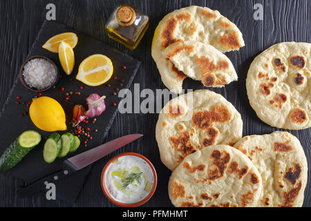 pan fried homemade hot pita bread on black wooden table,  fresh tzatziki sauce in bowl and ingredients on stone cutting board, view from above - Stock Photo