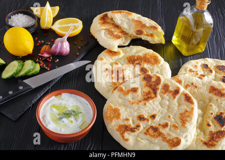 freshly baked hot pita bread on black wooden table,  fresh tzatziki sauce in bowl and ingredients on stone cutting board, view from above, close-up - Stock Photo