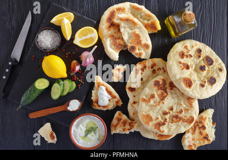freshly baked pita bread on black wooden table with savory tzatziki sauce. ingredients on stone cutting board, horizontal view from above - Stock Photo