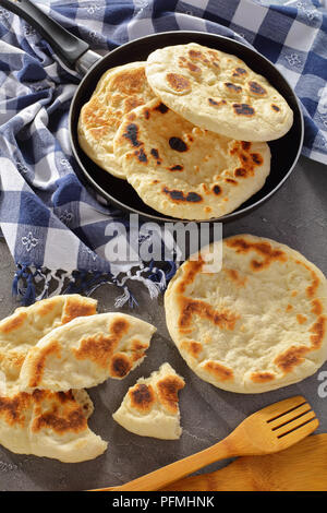 freshly fried pita bread in skillet with kitchen towel and wooden spatulas on concrete table, vertical view from above - Stock Photo