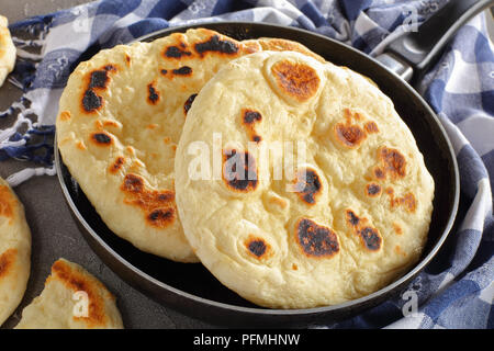 freshly pan fried pita bread in skillet with kitchen towel on concrete table, view from above, close-up - Stock Photo