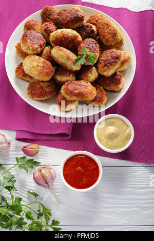 delicious fried hot meat cutlets on white plate with tomato sauce and mustard in  bowls on table,vertical view from above - Stock Photo