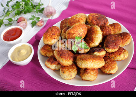 delicious fried hot meat cutlets on white plate with tomato sauce and mustard in  bowls on table,vertical view from above, close-up - Stock Photo