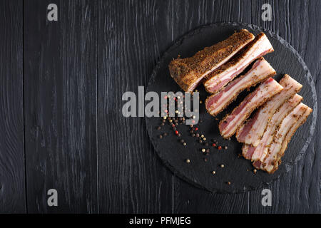 delicious spiced smoked speck cut in slices on black slate plate, view from above - Stock Photo