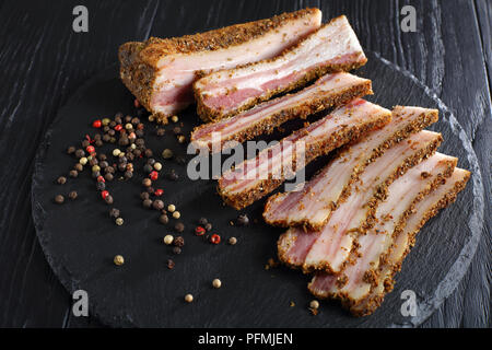 delicious spiced smoked speck cut in slices on black slate plate on wooden table, view from above, close-up - Stock Photo