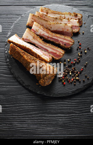 delicious spiced smoked speck cut in slices on black round stone plate on wooden table, vertical view from above - Stock Photo
