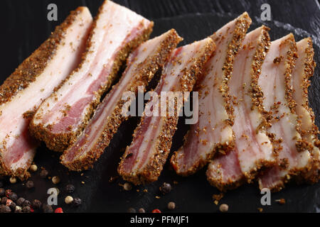 close-up of delicious spiced smoked speck cut in slices on black round stone plate on wooden table, horizontal view from above, macro - Stock Photo
