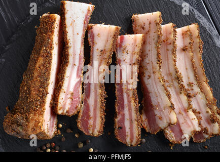 close-up of spicy smoked speck cut in slices on black round stone plate on wooden table, horizontal view from above - Stock Photo