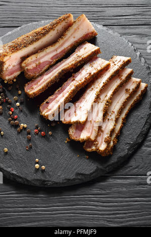delicious spicy smoked speck cut in slices on black round stone plate on wooden table,  vertical view from above - Stock Photo