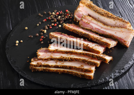 close-up of delicious sliced spicy smoked speck on black round stone plate on black wooden table, view from above - Stock Photo