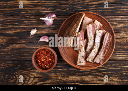 delicious sliced spicy air dried speck on clay plate on rustic wooden table with garlic  and chili flakes in bowl at background, horizontal view from  - Stock Photo