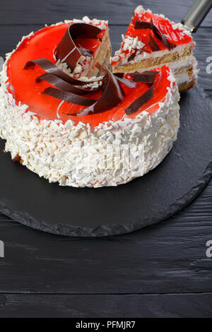 delicious torte layered with cream cheese mousse decorated with white chocolate flakes, red berry jelly and chocolate chips on black slate plate with  - Stock Photo