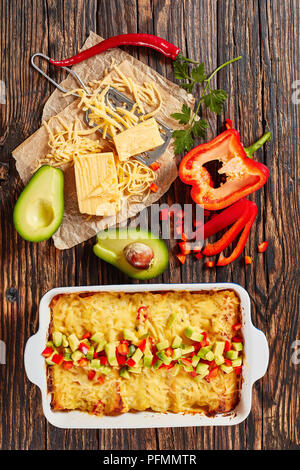 delicious hot homemade enchiladas of corn tortillas with shredded meat, sauce, grated cheese and pieces of chili in baking dish sprinkled with avocado - Stock Photo