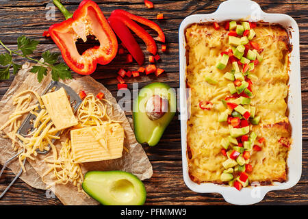 delicious homemade enchiladas of rolled corn tortillas stuffed with shredded meat, sauce, grated cheese and pieces of chili in baking dish sprinkled w - Stock Photo