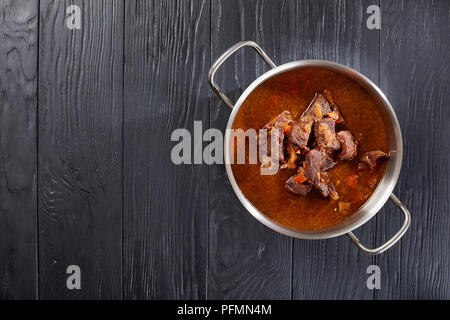 homemade hot Czech beef goulash in a stainless pan on black wooden table, view from above - Stock Photo