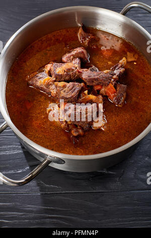 homemade hot Czech beef goulash in a stainless pan on black wooden table, vertical view from above - Stock Photo