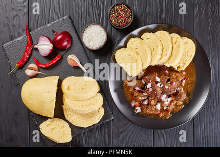 delicious homemade hot traditional Czech beef goulash served with steamed czech dumplings or knodel on black plate on wooden table with ingredients at - Stock Photo