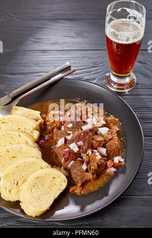 delicious homemade hot traditional Czech beef goulash served with steamed czech dumplings or knedliky on black plate on wooden table with glass of bee - Stock Photo