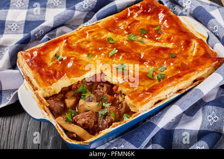 close-up of delicious Beef and Mushroom Pie topped with golden crust flaky puff pastry in a baking dish on wooden table, australian recipe, horizontal
