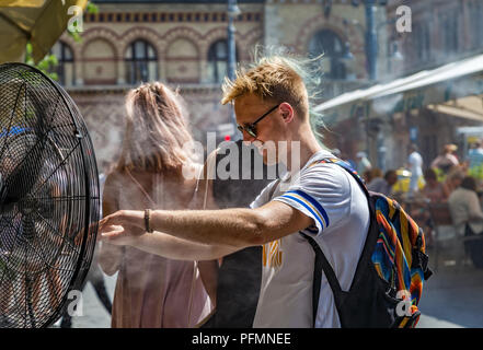 BUDAPEST,HUNGARY-AUGUST 09,2018:People alleviate the summer heat wave in front of the water spraying fan at the street of downtown. - Stock Photo
