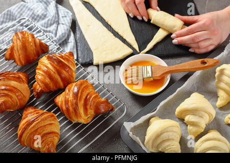 Woman is shaping layered yeast-leavened dough into crescent rolls to bake French croissants. freshly baked golden brown delicious hot croissants are c - Stock Photo