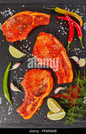 raw pork chops prepared to cook, marinated with spices and red sriracha sauce on black slate tray with chili pepper, salt, lime slices and spices, ver - Stock Photo