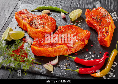 raw pork chops prepared to cook, marinated with spices and red sriracha sauce on black slate tray with chili pepper, salt, lime slices and spices, vie - Stock Photo