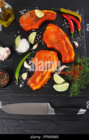 raw pork cutlets prepared to roast, marinated with spices and red sriracha sauce on black slate tray with chili pepper, salt, lime slices and spices o - Stock Photo