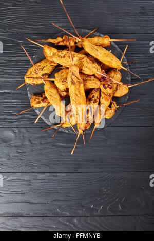 Chicken satay on skewers on a black stone tray on a wooden table, vertical view from above - Stock Photo
