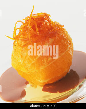 A caramelized orange topped with curls of zest sits in a puddle of rich, smooth chocolate custard. - Stock Photo