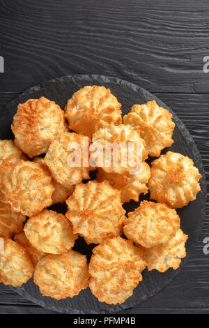 delicious coconut cookies on a plate on a black wooden table, vertical view from above - Stock Photo