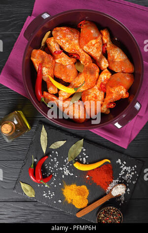 raw marinated chicken drumsticks rubbed with finely ground spice, chili pepper pieces, bay leaves  prepared to cook in a dish, ingredients on a stone  - Stock Photo