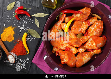 raw marinated chicken drumsticks sprinkled with spice, chili pepper pieces, bay leaves  prepared to cook in a dish, ingredients on a stone board on a  - Stock Photo
