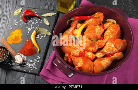 raw marinated chicken drumsticks sprinkled with spice, chili pepper pieces, bay leaves  prepared to cook in a dish, ingredients on a slate board on a  - Stock Photo