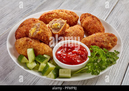 fried juicy breaded homemade meat croquettes with melted cheese filling on a white plate with cucumber salad and tomato sauce, view from above, close- - Stock Photo