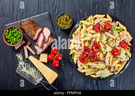 pasta penne salad with sliced ham, green peas, grated parmesan cheese, topped with grilled cherry tomatoes. ingredients and  pesto sauce at background - Stock Photo