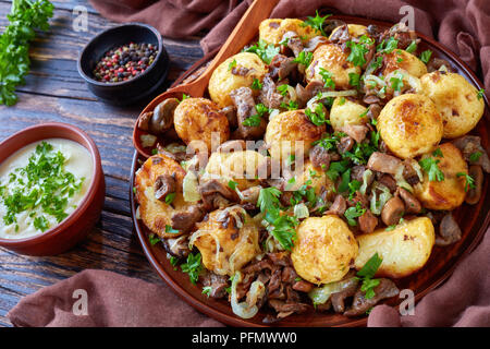 homemade sauteed new Potatoes with Wild Mushrooms, onion and spices on a plate with wooden spoon on an old rustic table with cream sauce, close-up - Stock Photo