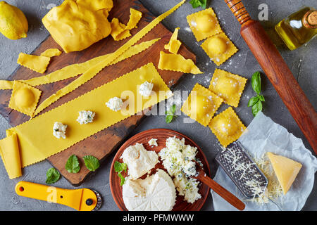 cooking up delicious ravioli with ricotta cheese filling mixed with finely chopped mint and basil leaves on a concrete kitchen table with ingredients, - Stock Photo