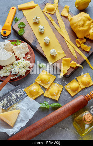 making up delicious ravioli with ricotta cheese filling mixed with finely chopped mint and basil leaves on a concrete kitchen table with ingredients,  - Stock Photo