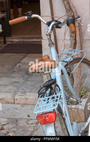 an old style vintage bicycle painted light blue with a leather saddle propped against a wall. - Stock Photo