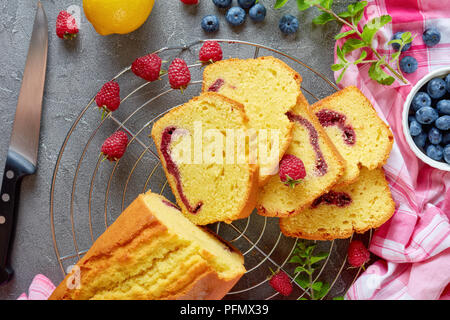freshly baked sliced lemon pound cake with berries jam filling also known as gateau de voyage cake on a concrete background with ingredients, french c - Stock Photo