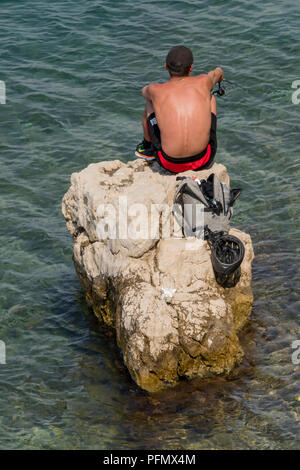 a young man sitting on a rock in the sea fishing in the sunshine. - Stock Photo
