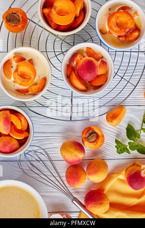 cooking a french dessert flagnarde with apricot. ingredients on a table, vertical view from above - Stock Photo