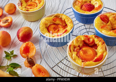 french summer dessert - Baked apricot clafoutis in ramekins placed on a wire rack and on a white table with fresh apricots, view from above - Stock Photo