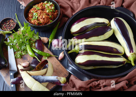 ingredients for cooking up Stuffed Eggplants, Aubergines - ragout of ground beef meat, tomatoes and onions and fresh eggplants in a baking dish and on - Stock Photo