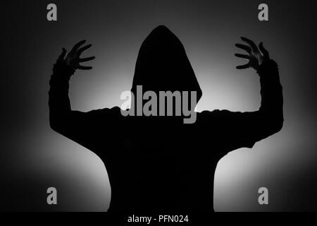 black and white photo: silhouette of a man in a hood holding a fantasy sword in - Stock Photo