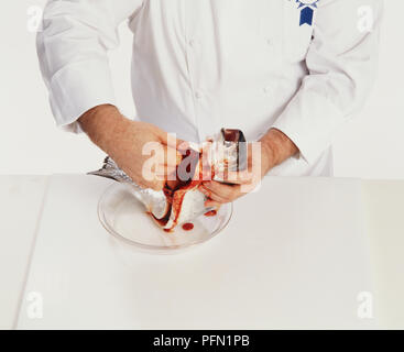 Chef gutting a fish, blood dripping into bowl underneath. - Stock Photo