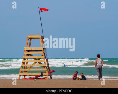 Chicago, Illinois, USA. 21st August 2018. Two children play in the sand while their mother stands by and a kayaker braves the waves at Montrose Beach. A red flag flies from a lifeguard stand indicating unsafe swiiming conditions caused by high surf and rip currents. Stiff northeast winds whipped up surf on Lake Michigan, bringing out kayakers, kite surfers and wave watchers. Credit: Todd Bannor/Alamy Live News - Stock Photo