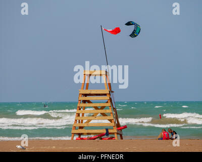 Chicago, Illinois, USA. 21st August 2018. A red flag indicating unsafe swimming conditions flies from a lifeguard stand at Montrose Beach as two children play in the sand and a kite surfer speeds by. Stiff northeast winds whipped up surf on Lake Michigan, bringing out kayakers, kite surfers and wave watchers. Credit: Todd Bannor/Alamy Live News - Stock Photo