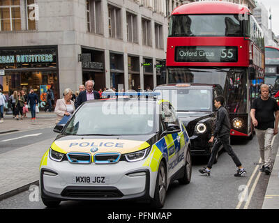 London, UK. 22nd August, 2018. Part of the effort to clean up the air in Oxford Street includes the introduction of electric or hybrid vehicles -  in this case a BMW electric Police Car, one of the new electric London Black cabs and a hybrid double decker London Bus. London 22 Aug 2018. Credit: Guy Bell/Alamy Live News - Stock Photo